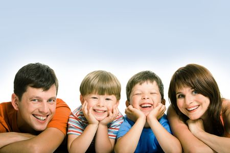 family line: Line of mother, father and their two sons looking at camera with happy smiles