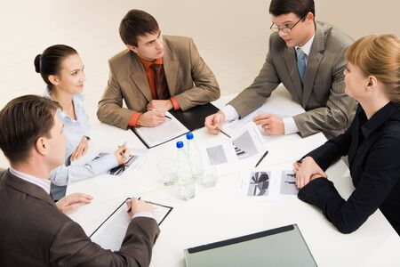 Group of five businesspeople discussing different questions gathered together around the table  Stock Photo - 3755499