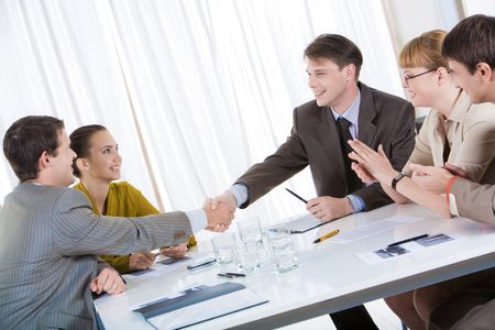 Image of confident partners shaking hands while their colleagues congratulating them photo