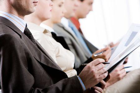 curso de capacitacion: Empresario de toma notas durante convenio con la fila de personas en estaciones de fondo