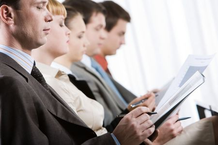 making notes: Row of confident business partners making notes during seminar Stock Photo