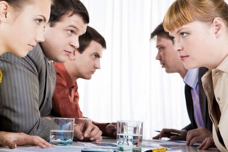 controversy: Profiles of serious employees sitting in two rows and looking at each other Stock Photo