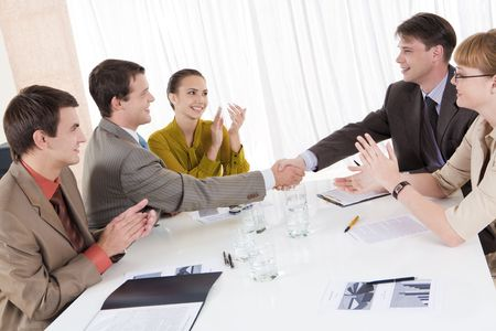 Image of confident partners shaking hands while their colleagues congratulating them Stock Photo - 3787744