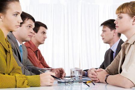 conflicto: Gente de negocios de dos filas frente a la mirada el uno al otro en serio