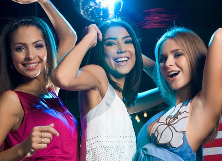 Portrait of three laughing girls dancing at disco in the night club Stock Photo - 3787754