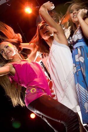 chicas bailando: Ver desde abajo de las ni�as glamoroso baile en discoteca Foto de archivo