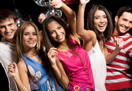 Portrait of glad teens looking at camera with smiles during party photo