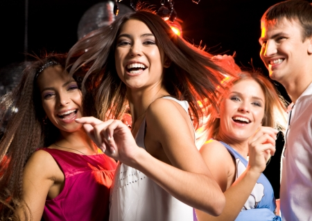people partying: Portrait of laughing girl wearing white dress dancing among her friends