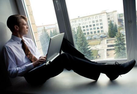 ceo: Photo of smart businessman sitting on window-sill with laptop and looking through window Stock Photo
