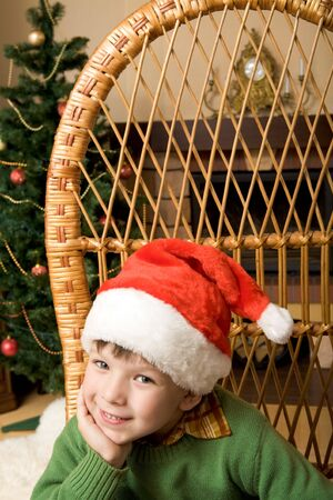 Portrait of boy wearing santa cap looking at camera with smile photo