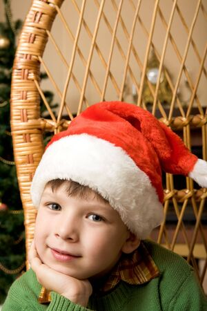 Adorable boy in Santa hat touching his face and looking at camera photo