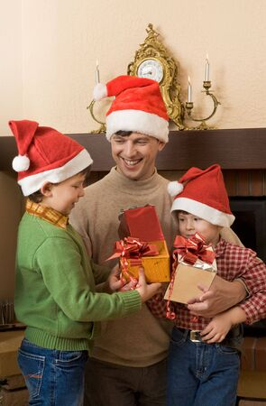 Portrait of father and his sons wearing santa hats with presents in hands photo