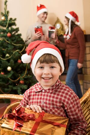 Happy lad with gift in hands looking at camera with smile on Christmas day photo