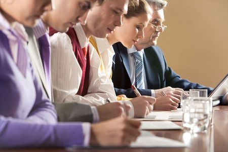 education success: Row of businesspeople writing review of their work with senior boss at background Stock Photo