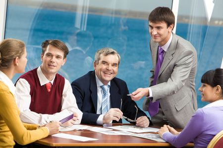 Confident managers talking about their work to colleagues during meeting photo