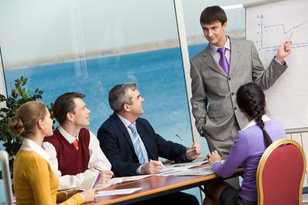 Young businessman standing near board and pointing at graph showing way to success photo