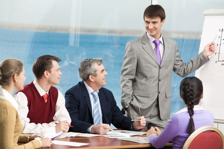 Group of business people listening to successful manager while he explaining his idea photo