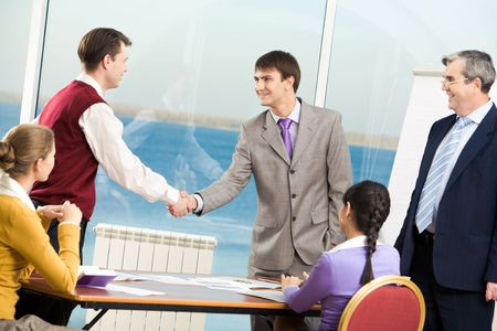 Businessmen handshaking after signing documents at meeting photo