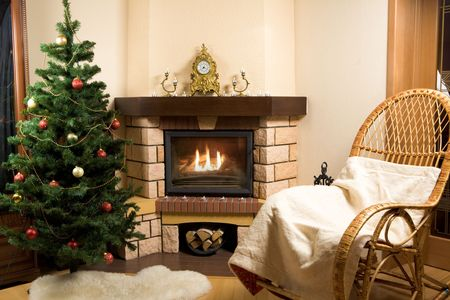 Image of house room with rocking-chair, Christmas tree, fireplace in it photo