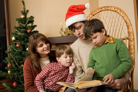 Portrait of friendly family looking into interesting book on Christmas day Stock Photo - 3851066