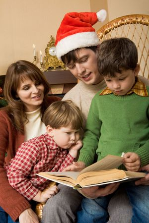 Portrait of four family members looking into book of fairy tales in boy�s hands Stock Photo - 3851067