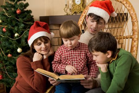 Little boy surrounded by his family members trying to read book Stock Photo - 3851065
