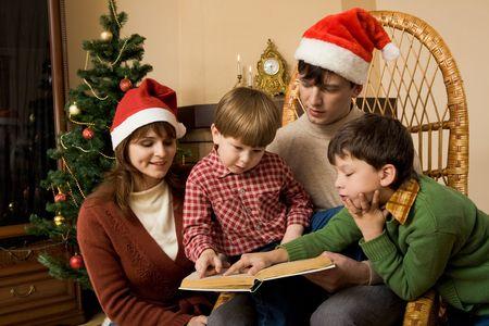 Imagen de los miembros de la familia leyendo cuentos de hadas en su casa junto Foto de archivo - 3851062