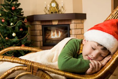 Photo of cute infant wearing santa cap sleeping in rocking chair under blanket photo