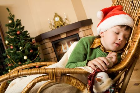 Image of innocent child having a snap on rocking chair on xmas evening photo