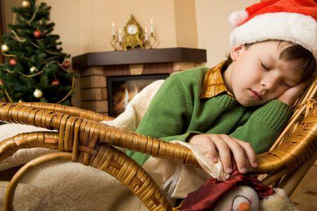 Sleeping lad in santa hat got tired on Christmas day photo