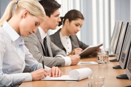 adult writing: Young businesswoman making notes in her notepad in working environment