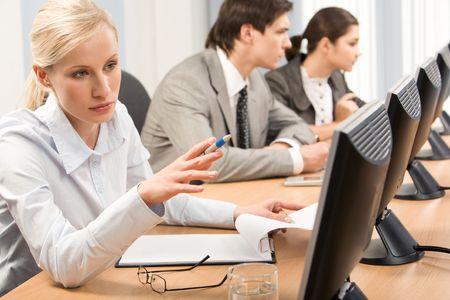 Successful professional pointing at computer monitor during seminar