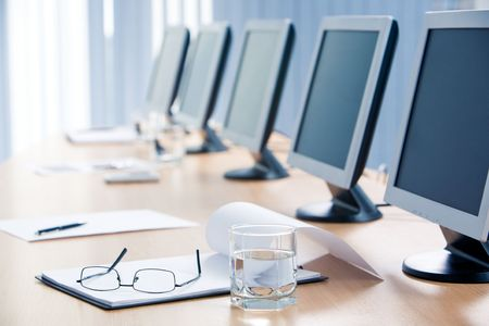 Close-up of workplace with notepad, glass of water, eyeglasses and monitors on it Stock Photo - 3858897