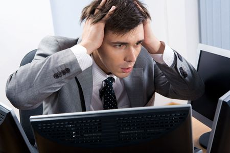 Portrait of frustrated employer sitting in front of computer with his hands on head photo
