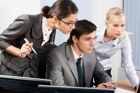 Three colleagues gazing at monitor with serious expressions during meeting