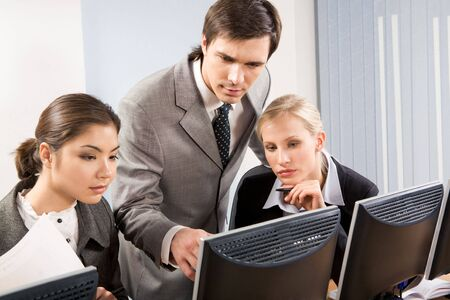 employees group: Serious businessman explaining something to his pretty colleagues while they looking at monitor