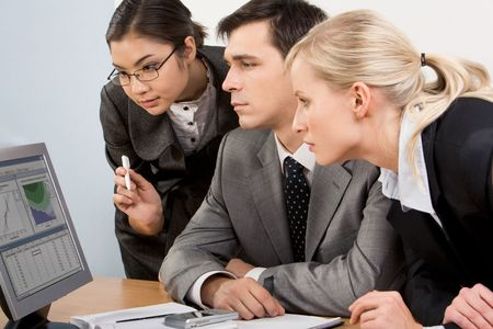 attentively: Image of smart work group staring at display of computer attentively