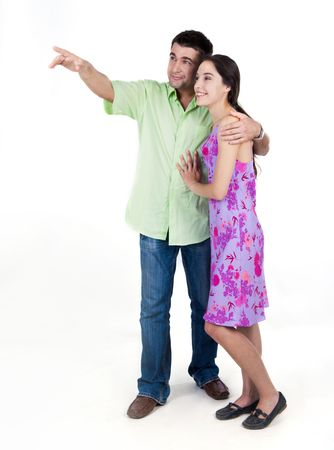 Portrait of young couple looking at something pointed at by man photo