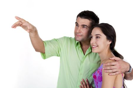 Handsome man embracing pretty woman while both looking at something over white background photo
