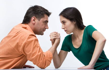 female wrestling: Man and woman doing arm wrestling showing their displeasure