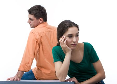 Sad woman sitting aback to boyfriend and touching her face Stock Photo
