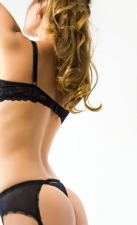 Aside view of beautiful female in black lingerie over white background