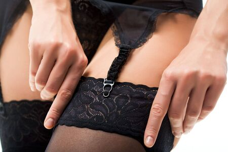 Close-up of female's hand putting on black stocking and fastening garter belt Stock Photo - 3850994