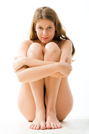 nude girl sitting: Portrait of sitting woman embracing her legs and looking at camera