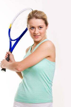 Portrait of pretty tennis player holding racket while waiting for ball photo
