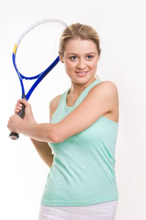 Cute girl prepared to push tennis ball with racket over white background photo
