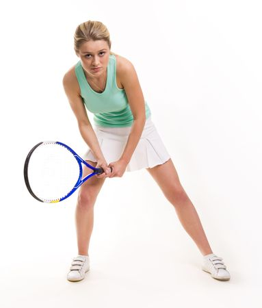 Serious woman with tennis racquet looking straight while waiting for a ball photo