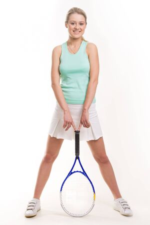 Smiling teenage girl standing and touching handle of tennis racket  photo