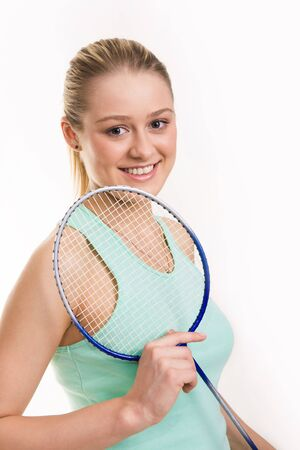 Portrait of attractive teenage girl with tennis racket in hand photo