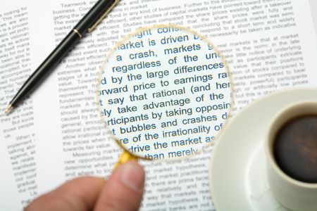 magnifying glass: Close-up of magnifying glass over paper with text on it with pen and coffee cup near by